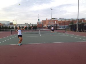 Senior and 2nd doubles player Liz Choi prepares to hit a serve in the third set with fellow senior and partner Raveesha Aurora.
