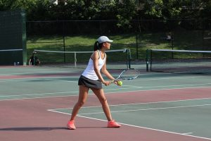 First doubles player and junior Isabelle Zhou prepares to serve.